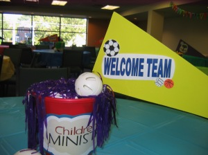 Table centerpieces:  sand buckets, pom poms, balls, and foam pennants with the names of each ministry area